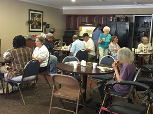 Seniors enjoying an event in a clubhouse.